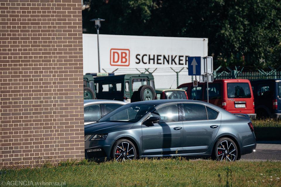 Dwie Skody Octavie RS stoją na placu komendy SG. Czarna skoda komendanta jest garażowana.