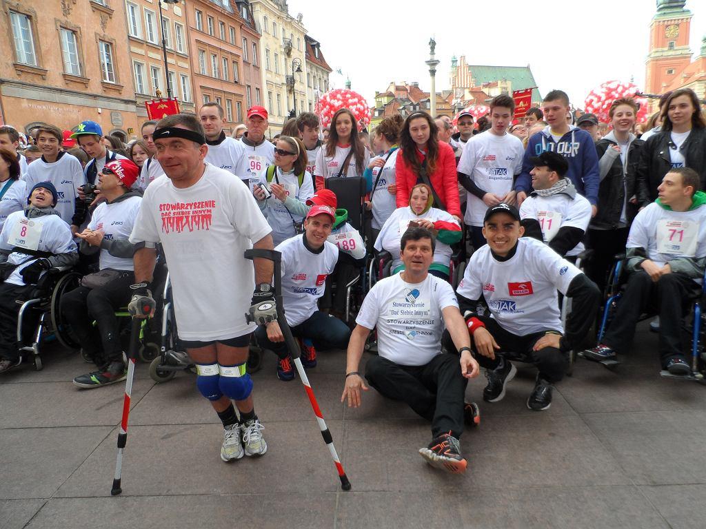 Bieg charytatywny przed Orlen Warsaw Marathon 2014. Janusz Bukowski siedzi na pierwszym planie. Po prawej Adam Kszczot, a po lewej Marcin Lewandowski i Zbigniew Stefaniak