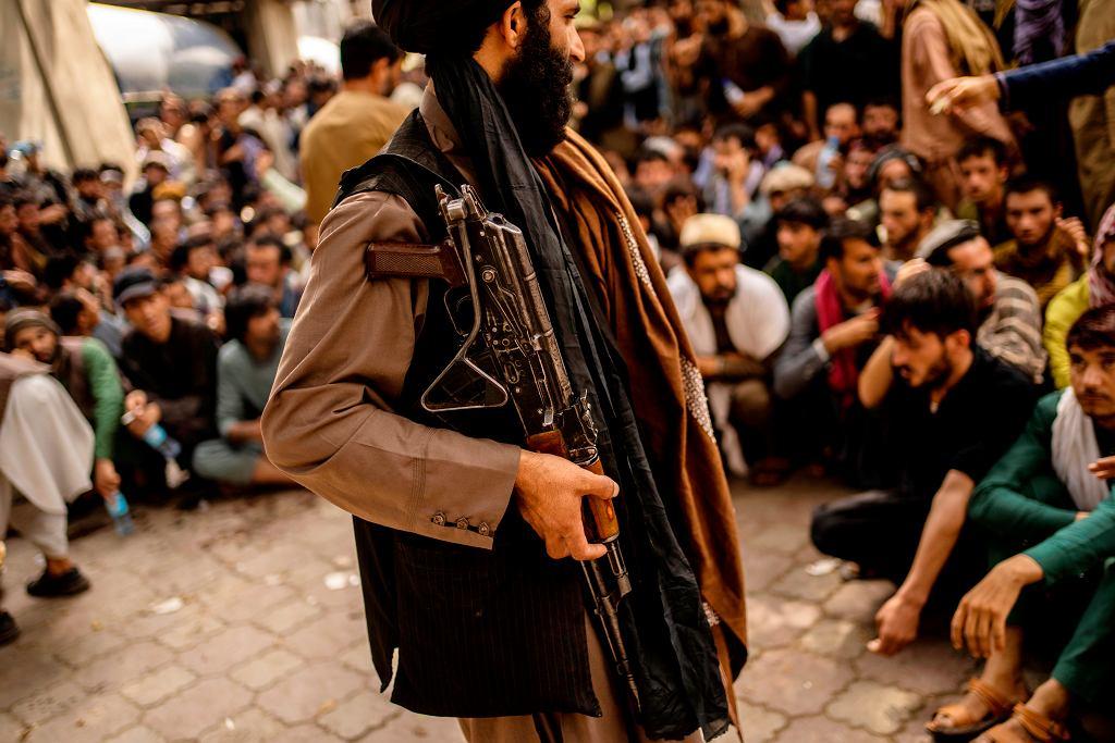 Talibowie kontrolują tłum czekający na wypłacenie pieniędzy z bankomatu. Afganistan, Kabul, 12 września 2021 r.