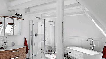 <B> Monotonia bywa męcząca - nie tylko w życiu, ale także w mieszkaniu. Na przykład łazienka zaaranżowana w neutralnych barwach będzie wprawdzie zawsze na czasie, ale łatwo się może znudzić. Dlatego radzimy: wprowadź akcent w mocnym kolorze. Nawet pojedynczy potrafi zdziałać cuda. </B><BR />  Głównym akcentem kolorystycznym w białej łazience, a właściwie komfortowym pokoju kąpielowym, są położone na podłodze płytki ceramiczne z graficzno-kwiatowym wzorem w dwóch mocnych barwach: czerwieni i granatu. Pomieszczenie znajduje się na poddaszu, stąd skośne ściany, belki stropowe i słup konstrukcyjny. Drewniane elementy architektoniczne często pozostawia się w naturalnym kolorze, by dodać wnętrzu przytulności i podkreślić jego strychowy charakter. Tutaj zdecydowano się je pomalować na kolor ścian i sufitu, przez co wnętrze wydaje się jeszcze większe. Białe są również  łazienkowe urządzenia o prostych formach, które wtapiają się w tło i nie rzucają się w oczy.