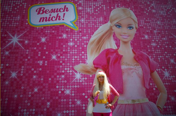 """Model Ina Blaubeer poses with a Barbie doll in front a """"Barbie Dreamhouse"""" of Mattel's Barbie dolls in Berlin, May 16, 2013. The life-sized house, covering about 1,400 square metres offers visitors to try on Barbie's clothes in her walk-in closet, tour her living room and her kitchen. REUTERS/Pawel Kopczynski (GERMANY  - Tags: SOCIETY ENTERTAINMENT)"""