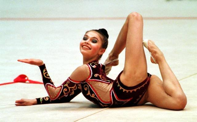 Alina Kabayeva, top  Russian rhythmic gymnastics shows her flexibility as she takes part in 1999 Grand Prix rhythmic gymnastics tournament in Kiev, Ukraine, on Saturday, March 13, 1999. Current rhythmic gymnastics from 26 countries took part in this greatest competition. (AP Photo/Efrem Lukatsky)