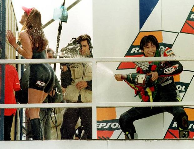 Japan's Kazuto Sakata, right, sprays one of the podium girls with champagne after winning the 125cc British Motorcycle Grand Prix, at Donington Park Sunday July 5 1998. (AP Photo/Danielle Smith)