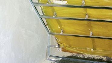 Źle ocieplone poddasze; pod paroizolacją widoczna jest tylko jedna warstwa wełny, ułożona między krokwiami