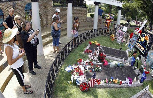 In this Aug. 10, 2010 photo, tourists view Elvis Presley's grave in Meditation Garden at Graceland, Presley's home in Memphis, Tenn. CKx Inc., owner of the
