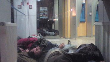 Bezdomni nocują w pomieszczeniu banku PKO BP przy hotelu Polonia