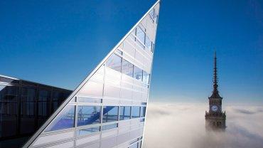 Warszawa przykryta chmurami. Ponad nimi wyłącznie fragmenty najwyższych budynków. Widok z ostatnich pięter apartamentowca Złota 44 na zegar na szczycie Pałacu Kultury jest absolutnie wyjątkowy.