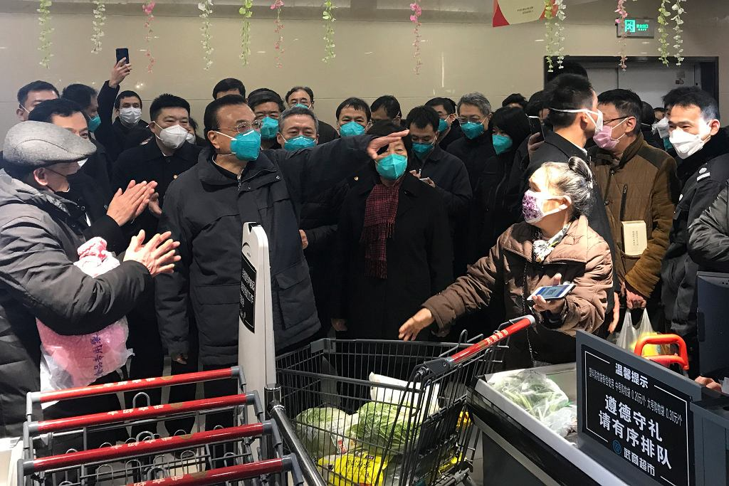 Premier Li Keqiang (w środku, gestukuluje) odwiedził Wuhan 27 stycznia. Na zdjęciu podczas wizyty w supermarkecie