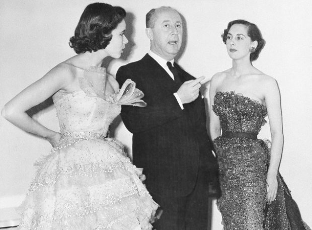 French fashion designer Christian Dior is seen with two unidentified models displaying his fashion designs at Londons Savoy Hotel, April 28, 1950.  He calls the creation at left