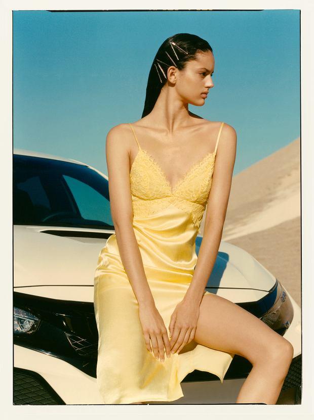 Satynowa sukienka na cienkich ramiączkach i koronkowym wykończeniem oraz rozcięciem z przodu.