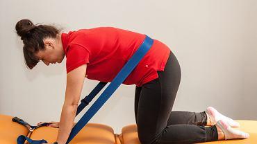 Ćwiczenie na bóle kręgosłupa lędźwiowego z zastosowaniem pasa (mobilizacja czynna skłonu tułowia w przód). Pas zahaczamy na wysokości bolesnego segmentu; pozycja wyjściowa