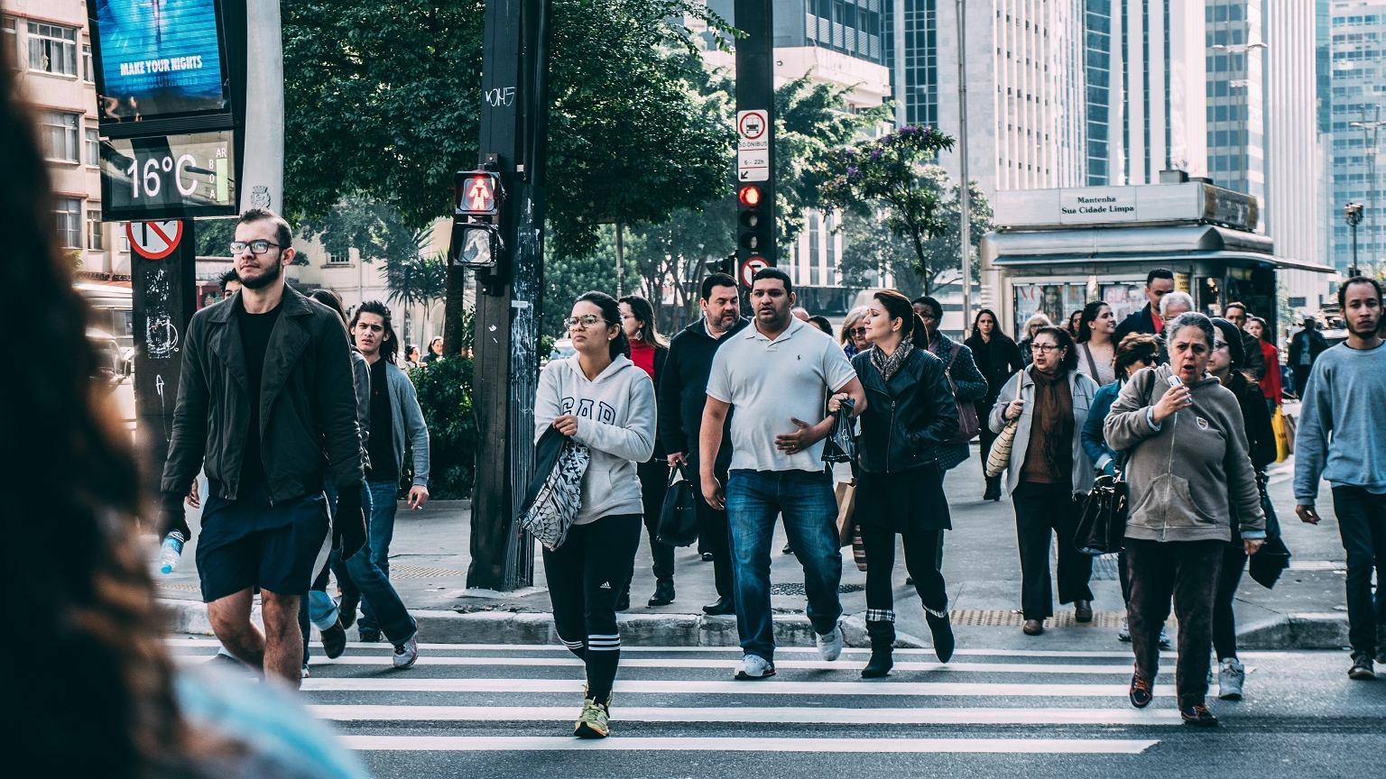 Ludzie przechodzący przez ulicę w ruchliwym mieście
