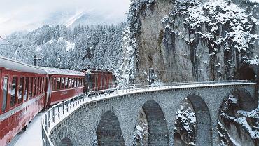 Czerwony pociąg pośród śnieżnych szczytów.