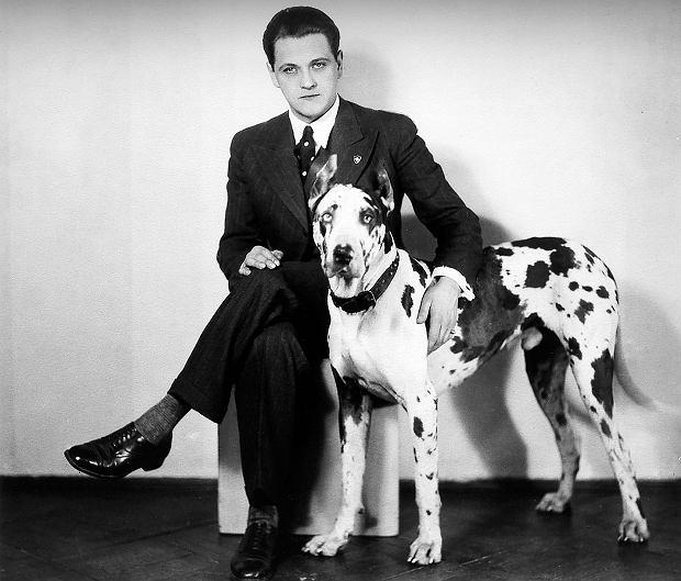 Eugeniusz Bodo ze swoim dogiem arlekinem Sambo, który zaginął w powstaniu warszawskim. Zdjęcie zrobiono w latach 30., kiedy aktor był u szczytu kariery. Jego wielbiciele śledzili prasę w nadziei, że napisze, w co się ubrał, ponieważ aktor uchodził za arbitra elegancji. Czerpał z tego zresztą spore zyski, zarabiając na reklamach koszul czy butów. Nigdy nie reklamował alkoholu. Po incydencie w 1929 r., kiedy prowadząc swojego chevroleta, spowodował wypadek, w którym zginął jego kolega, już nigdy nie tknął alkoholu.