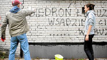 Dziennikarze Gazety Wyborczej zamalowują wulgarne napisy. 2013 r.