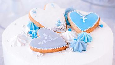 Tort na chrzciny ozdobiony jest elementami, które kojarzą się z tym sakramentem - na przykład szatką czy świecą