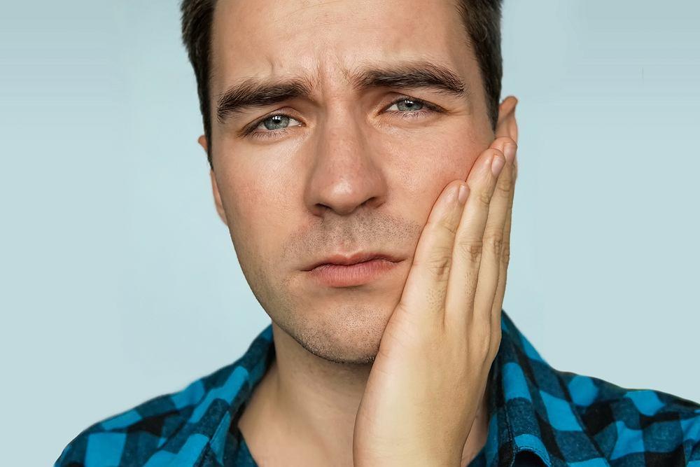 Ból żuchwy często pojawia się na skutek problemów stomatologicznych
