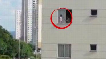 Małe dziecko na parapecie na wysokości trzeciego piętra