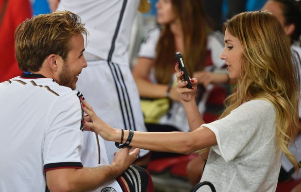 Germany's Mario Goetze has his photo taken by his girlfriend Ann-Kathrin Broemmel after the World Cup final soccer match between Germany and Argentina at the Maracana Stadium in Rio de Janeiro, Brazil, Sunday, July 13, 2014. Germany won the match 1-0. (AP Photo/Martin Meissner)