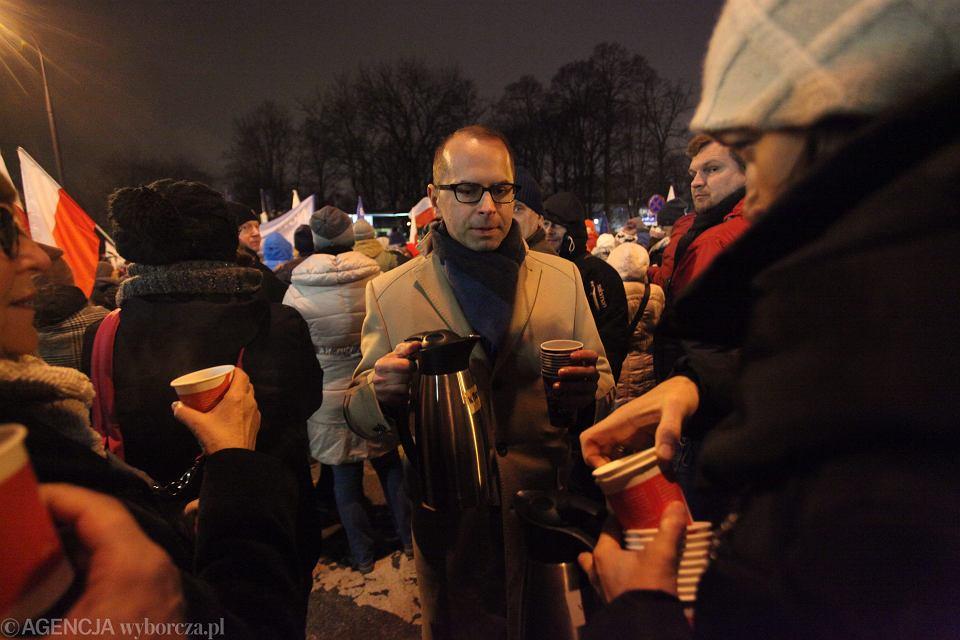 Poseł Michał Szczerba serwuje gorącą herbatę podczas demonstracji pod sejmem