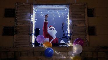 Koronawirus. Francuski tenor Stephane Senechal, przebrany za Świętego Mikołaja, śpiewa świąteczne utwory z okna swojego mieszkania w Paryżu, w czasie częściowego lockdownu. 15 grudnia 2020 r.