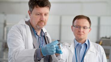 Dr Jacek Rzadkiewicz (z lewej) i dr Rafał Prokopowicz z zasobnikiem do napromieniania próbek w celu produkcji renu 186m
