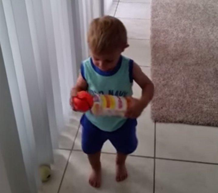 Mały chłopiec próbuje posprzątać zabawki