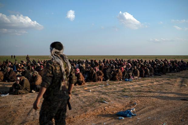 Bojownik Syryjskich Sił Demokratycznych pilnuje mężczyzn z Baghouz, ostatniej twierdzi Państwa Islamskiego