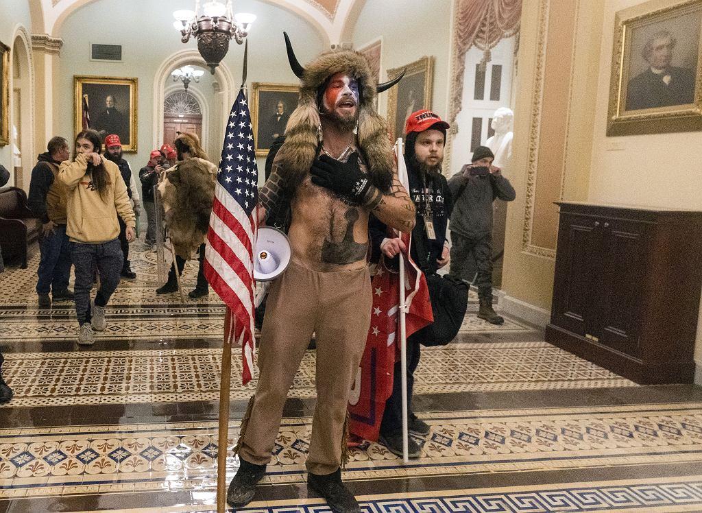 Jake Angeli, jeden z najbardziej znanych wyznawców teorii spiskowej pod nazwą QAnon, podczas szturmu trumpistów' na Kapitol. Donald Trump nie uznał porażki w wyborach i na Twitterze podżega swoich zwolenników do ataku. Zginęły cztery osoby. Waszyngton, USA, 6 stycznia 2021