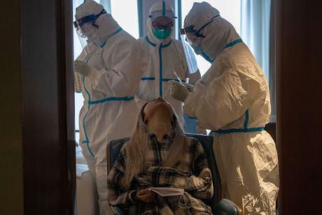 31.03.2020 Chiny, Wuhan. Pobieranie próbek do testu na obecność koronawirusa u kobiety przebywającej na kwarantannie.