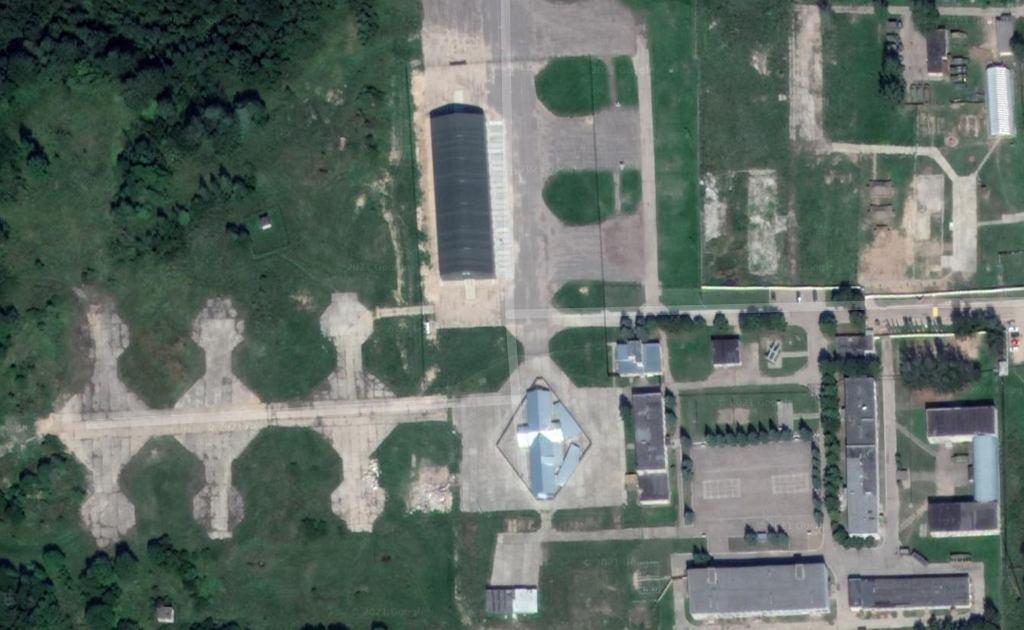 Podłużna czarna hala i stojący obok budynek ze srebrnej blachy falistej. Tam są szczątki Tu-154M numer 101