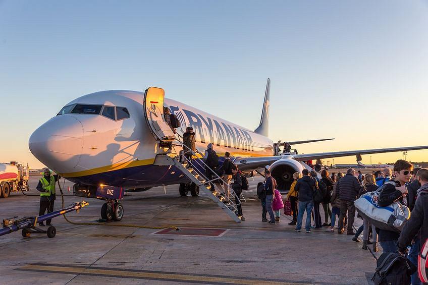 Pasażerowie wsiadają do samolotu linii Ryanair na lotnisku w hiszpańskiej Walencji  .