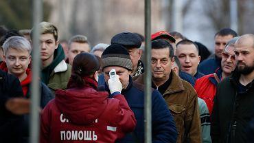 28.03.2020, Horodziej, Białoruś, służby medyczne sprawdzają temperaturę kibicom wchodzącym na mecz pierwszej ligi piłki nożnej FK Horodziej - Nioma Grodno