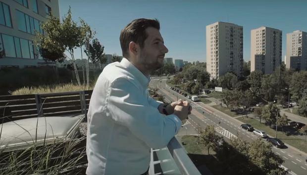 Patryk Jaki spogląda na blokowisko z balkonu nowoczesnego osiedla