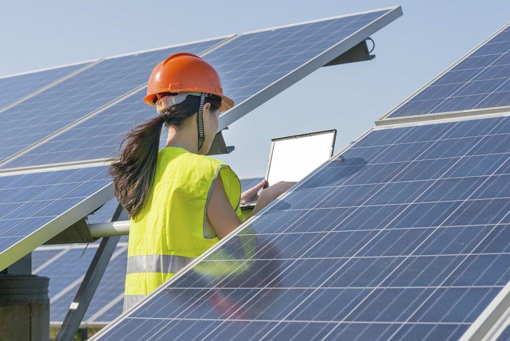 Inżynier pracuje przy panelu słonecznym (fot. Lawren Lu/istockphoto)