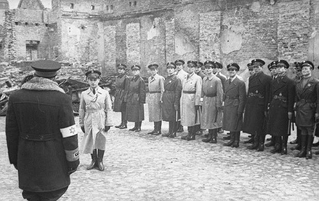 Odprawa oddziału żydowskiej Służby Porządkowej w getcie warszawskim w 1941 r. Tyłem stoi twórca tej formacji Józef Szeryński. Przed wojną pracował w Komendzie Głównej Policji Państwowej, ochrzcił się i odciął od żydowskich korzeni. Głosił antysemickie hasła i wstąpił do sanacyjnego Obozu Zjednoczenia Narodowego. Szeryński wobec mieszkańców getta był brutalny i bezwzględny, brał łapówki, prowadził szemrane interesy. Ściśle współpracował z Niemcami, wiadomo jednak, że w listopadzie 1941 r. odmówił rozstrzelania Żydów z Gęsiówki i egzekucję musiała wykonać granatowa policja. Meldunek Szeryńskiemu składa jego zastępca Jakub Lejkin, z zawodu adwokat. Lejkina, który wsławił się brutalnością wobec mieszkańców getta, zastrzelił Eliasz Różański z Żydowskiej Organizacji Bojowej