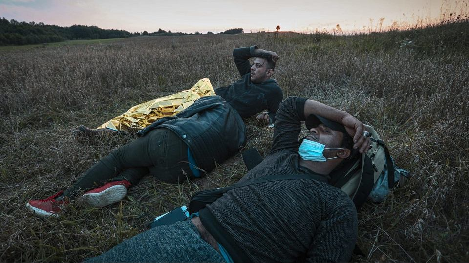 Mohammed (l) and Sfaa (R) are seen completely exhausted in a field near the border on 14 August, 2021 in Minkowce, Poland.