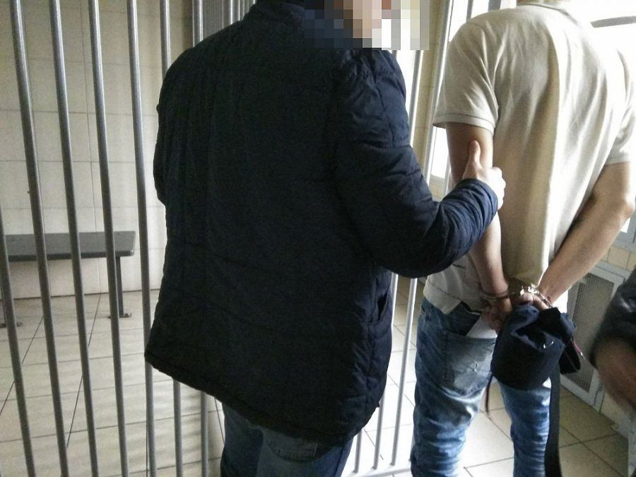 Policjant wykonuje czynności z zatrzymanym