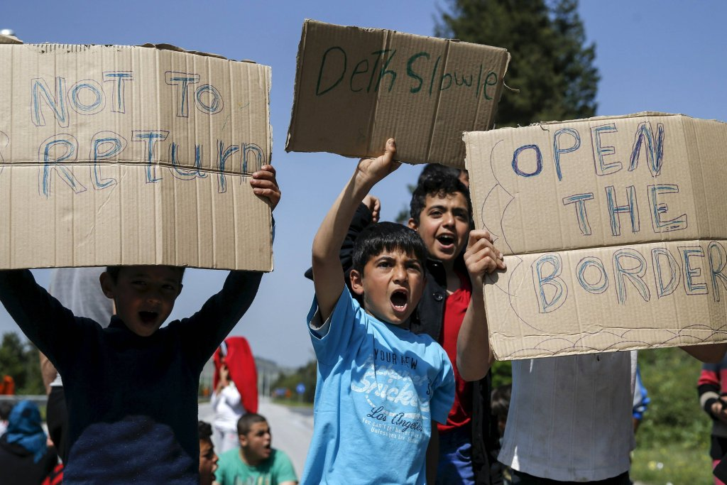 yMigrants and refugees shout slogans as they block the highway near the Greek-Macedonian border near the village of Evzoni