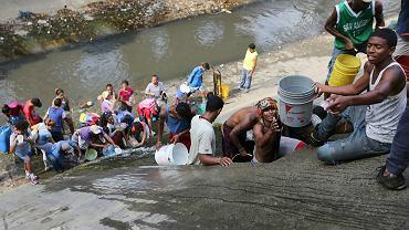 Najbardziej zrozpaczeni albo lekkomyślni mieszkańcy Caracas nabierają wodę prosto z Guaire - przecinającej stolicę brunatnej, cuchnącej rzeki-ścieku. 11 marca 2019 r.