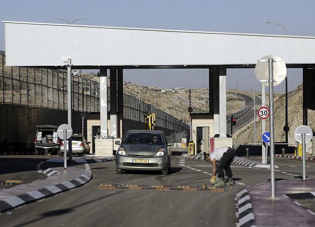 Jeden z punktów kontrolnych na autostradzie łączącej Tel Awiw z Jerozolimą. Armia izraelska ustawiła je w miejscach, w których droga przecina granicę z Autonomią Palestyńską. Dzięki temu w każdej chwili może zatrzymać Palestyńczyków na granicy. Natomiast Izraelczycy jeżdżą do Autonomii bez przeszkód - przeznaczona dla nich część autostrady jest za wysokim murem (na zdjęciu po lewej stronie).
