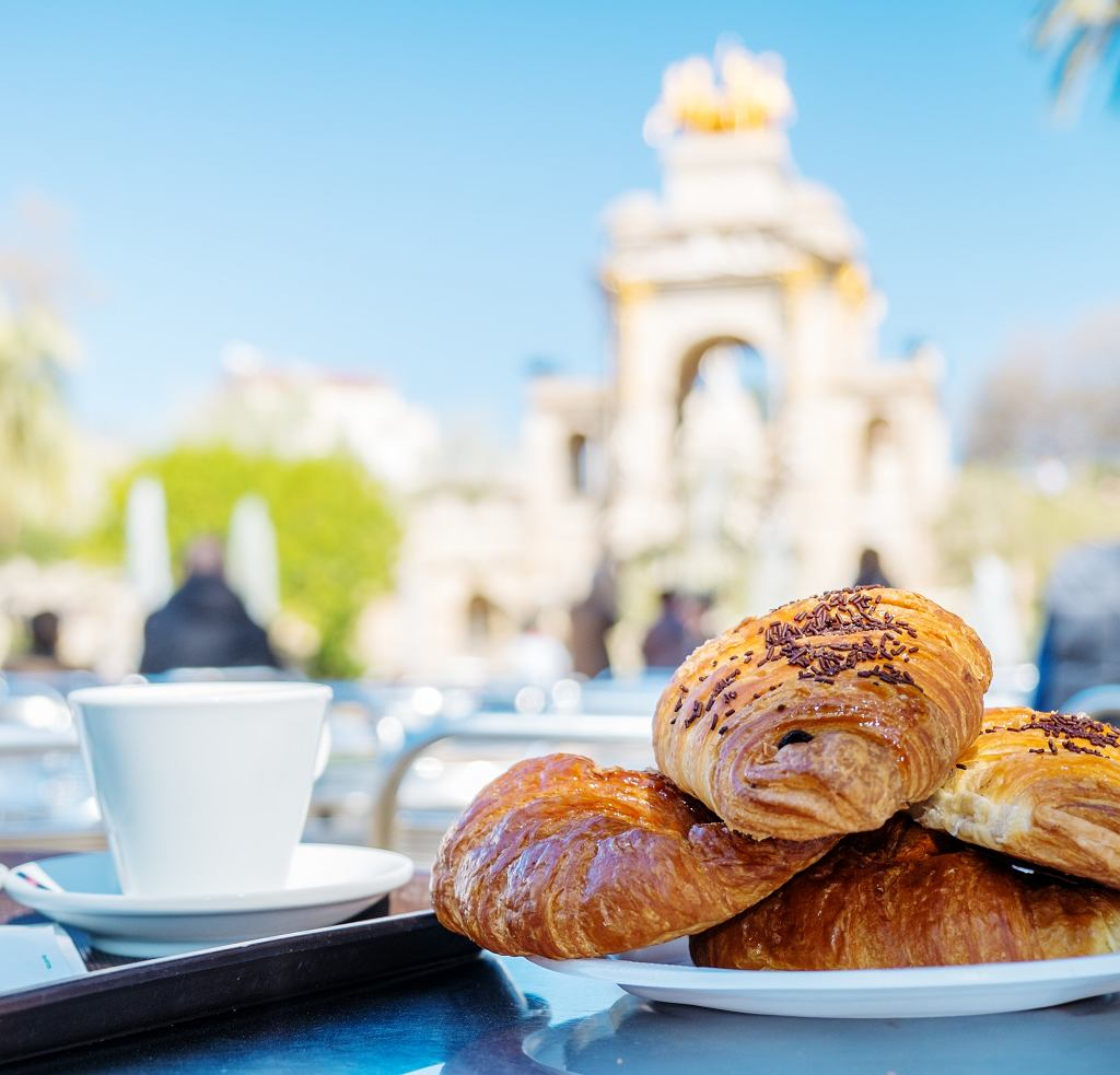 Tasty croissants with cup of coffee against famous fountain view in Barcelona