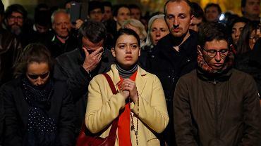 Pożar katedry Notre Dame w Paryżu, ludzie modlący się na ulicy w pobliżu tragedii.