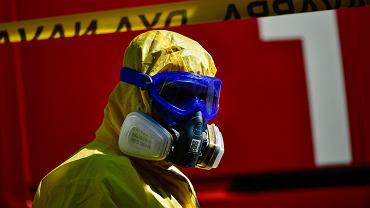 26.03.2020, Pamplona, Hiszpania, wolontariusz zajmujący się dezynfekcją karetki po przewiezieniu pacjenta zarażonego koronawirusem.
