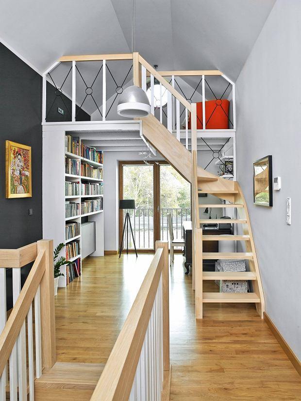 Na dole biblioteczka imiejsce do pracy, na górze - kącik do czytania, wktórym można się zaszyć wieczorem zksiążką wręku. Ado tego nie trzeba wiele, wystarczy wygodny fotel idobra lampa.