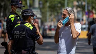 Policjanci proszą mężczyznę o założenie maski na twarz w Barcelonie w Hiszpanii