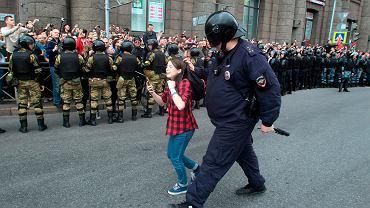 Policjant prowadzi nastolatkę podczas zamieszek w Petersburgu, wrzesień 2018 r.