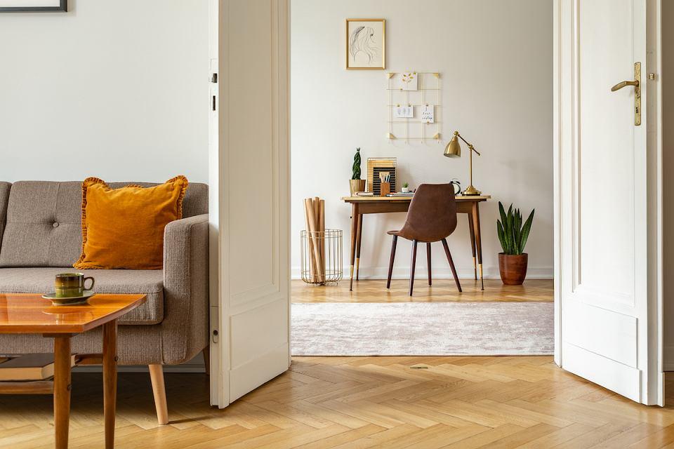 Musztardowa poduszka dekoracyjna świetnie pasuje do szarej sofy, drewna i bieli.
