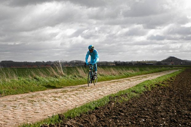 An Astana team cyclist trains ahead of Sunday's 114th edition of the Paris-Roubaix cycling classic, in Haveluy, northern France, Thursday, April 7, 2016. The Paris-Roubaix cycling classic is a 257.5 kilometer (160 mile) one day cycle race, with about 20 per cent of the distance run on cobblestones, (AP Photo/Michel Spingler)