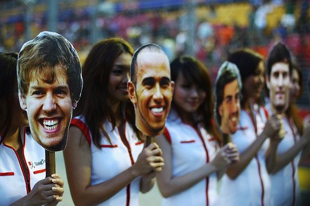 SINGAPORE - SEPTEMBER 25: (L-R) Grid girls wear masks featuring Sebastian Vettel, Lewis Hamilton, Fernando Alonso and Mark Webber before the Singapore Formula One Grand Prix at the Marina Bay Street Circuit on September 25, 2011 in Singapore. (Photo by Vladimir Rys/Getty Images)